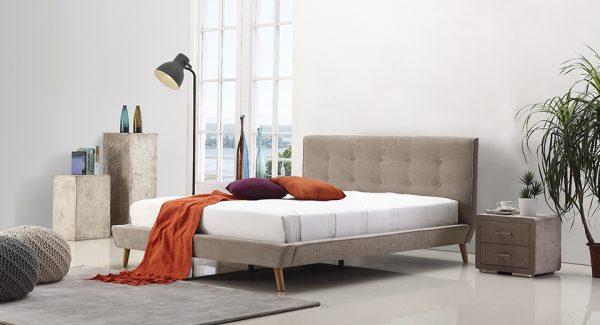 חדר שינה עם מיטה זוגית מעוצבת מרופדת בד מיקרופייבר בצבע חום אפרפר
